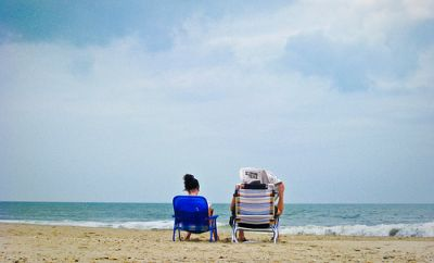 Two people sitting on beach in chairs